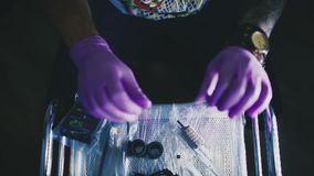 Tattoo master selects the needle to work stock video