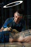 Tattoo master at work in studio Royalty Free Stock Photos