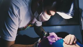 Tattoo master works with concentration stock video