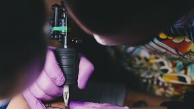 Tattoo master works with a tattoo machine stock video footage