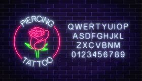 Tattoo and piercing parlor glowing neon signboard with rose emblem and alphabet. Flower symbol in circle frame. With text. Vector illustration Stock Photos