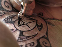 Tattoo in Progress. Close up view of a tattoo artist's hands at work Royalty Free Stock Images