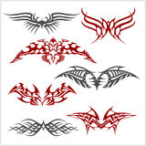 Tattoo set in tribal style on white background. Symmetric tattoo set in tribal style on white background Stock Photo