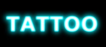 Tattoo shop blue neon sign. Neon tattoo sign in shop window A tattoo shop that offers custom design tattoos, as well as body piercings in the nose, lip, navel royalty free stock images