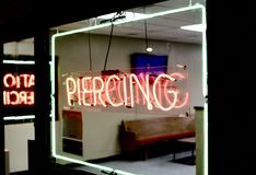 Piercing and tattoo shop neon sign. A tattoo shop that offers custom design tattoos, as well as body piercings in the nose, lip, navel and genitals royalty free stock photography