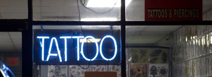 Tattoo shop blue neon sign. A tattoo shop that offers custom design tattoos, as well as body piercings in the nose, lip, navel and genitals stock photos