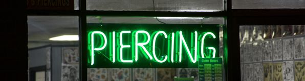 Piercing and tattoo shop green neon sign. A tattoo shop that offers custom design tattoos, as well as body piercings in the nose, lip, navel and genitals stock image