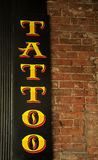 Tattoo Sign. A yellow, black and red tattoo sign hanging on a brick wall stock photo