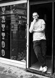 Tattoo Soho. Man with tattoos on arm standing in a Tattoo Parlour doorway in Soho, London. W1 Royalty Free Stock Images