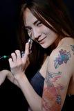 Tattoo woman artist holding tattoo machine on dark background. Tattoo asian woman artist holding tattoo machine on dark background stock image