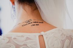 Tattoo words from the Bible on bridal neck Stock Photos