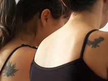 Tattoo02. Two women with their tattoos stock photos