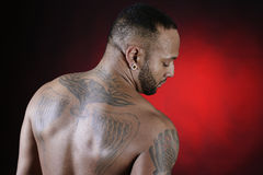 Tattooed African American Young Man. Tattooed african american young man backwards in a red background royalty free stock photo