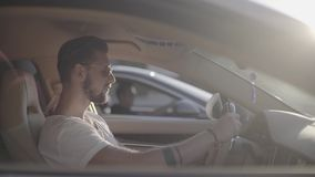 Tattooed attractive handsome young man in sunglasses sitting in luxury sport racing car opposite to rival ready to start. A car race on empty highway road stock footage