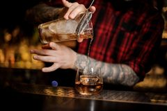 Tattooed barman pouring fresh drink into a whiskey dof glass stock image