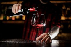 Tattooed barman pouring red wine into the burgunya glass stock photo