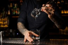 Tattooed barman putting an ice cube into a cocktail glass stock images