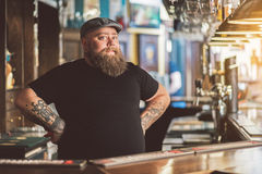 Tattooed barman working in pub royalty free stock image