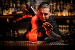 Tattooed bartender adding spices powder into a cocktail glass wi royalty free stock images