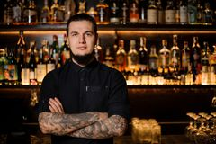 Tattooed bartender standing on the background of the bar stock photography