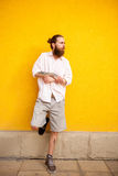Tattooed bearded attractive man on yellow wall Royalty Free Stock Photography