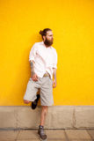 Tattooed bearded attractive man on yellow wall Royalty Free Stock Image