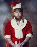 A man dressed in Santa clothes holds Longboard. A tattooed, bearded hipster male dressed in Santa clothes holds Longboard royalty free stock photo