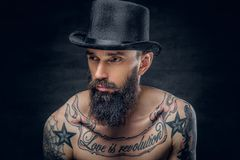 Tattooed bearded male in cylinder hat. Close up portrait of bearded male in top hat with tattoos on his chest over dark background Stock Image
