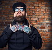 Tattooed bearded male in military jacket. Stock Photos