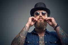 Tattooed bearded male in sunglasses and top hat. Studio portrait of stylish bearded male with a tattoo on his chest, dressed in a denim shirt, cylinder hat and Stock Photo