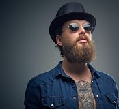 Tattooed bearded male in sunglasses and top hat. Studio portrait of stylish bearded male with a tattoo on his chest, dressed in a denim shirt, cylinder hat and Stock Image
