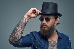Tattooed bearded male in sunglasses and top hat. Studio portrait of stylish bearded male with a tattoo on his chest, dressed in a denim shirt, cylinder hat and Royalty Free Stock Image
