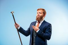 Tattooed bearded man in a suit holding cane. Isolated on a blue background Royalty Free Stock Photography