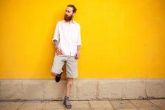 Tattooed bearded man on yellow wall Stock Image
