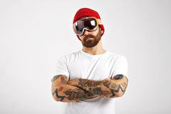 Tattooed and bearded snowboarder in blank white t-shirt. Portrait of a fit young man wearing a red knitted hat, skiing goggles and a plain white t-shirt isolated Royalty Free Stock Image