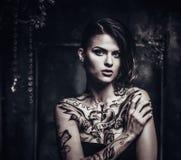 Tattooed beautiful woman. In old spooky interior Stock Photo