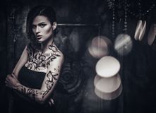 Tattooed beautiful woman. In old spooky interior Royalty Free Stock Photo