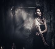 Tattooed beautiful woman. In old spooky interior Royalty Free Stock Photos
