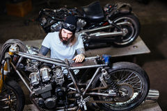 Tattooed Biker Assembling Motorcycle in Garage. Portrait of tattooed man working in garage customizing motorcycle and repairing broken parts stock photography