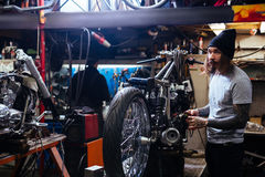 Tattooed Biker Repairing Motorcycle in Garage. Side view portrait of bearded tattooed man working in garage tuning motorcycle and repairing broken parts stock photography