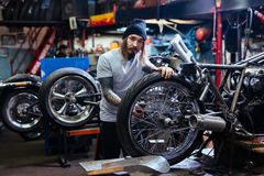 Tattooed Biker Working on Motorcycle in Garage. Portrait of bearded tattooed man working in garage tuning motorcycle and looking at camera stock photo