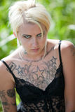 Tattooed blonde woman standing in field Royalty Free Stock Images