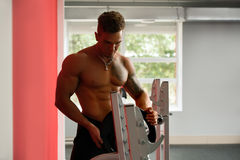 Tattooed bodybuilder puts weight plate on barbell Royalty Free Stock Photography