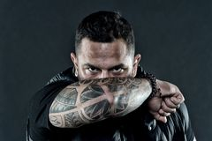 Tattooed elbow hide male face dark background. Visual culture concept. Tattoo can function as sign of commitment. Do. Tattoos hide lack of masculinity. Man stock photography