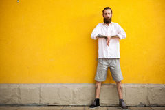 Tattooed fashion bearded hipster on yellow wall. Posing outdoor Royalty Free Stock Photos