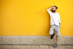 Tattooed fashion bearded hipster on yellow wall. Posing outdoor Royalty Free Stock Photo
