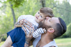 Tattooed father have fun with his son. In the park Royalty Free Stock Photography