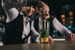 tattooed female bartender showing colleague how to prepare drink royalty free stock image