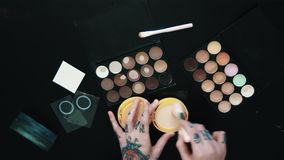 Tattooed female hands uses makeup brush beige powder puff-box over black table