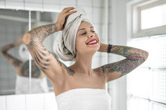 Tattooed girl in bathroom. Attractive smiling girl with colorful tattoos stands with closed eyes in the bathroom. She has white towels on her body and her head stock image
